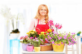 Female horticulturist standing with flowers — Stock Photo