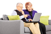 Mature couple looking at laptop — Stock Photo