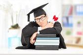 Worried college graduate on books — Stock Photo