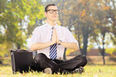 Businessperson with eyeglasses doing yoga exercise seated on a   — Stock Photo