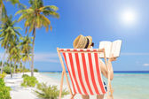 Man reading book on beach — Stock Photo