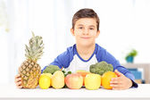 Boy sitting with fruits and vegetables — Stock Photo
