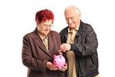 Couple putting coin into piggy bank — Stock Photo
