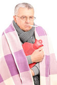 Sick senior with thermometer in mouth — Stock Photo