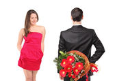Man hiding flowers and woman — Stock Photo