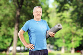 Man holding an exercising mat in park — Stock Photo