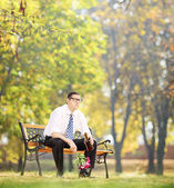 Disappointed man holding bottle in park — Stock Photo