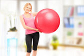 Blond female athlete holding a pilates ball and posing indoor — ストック写真