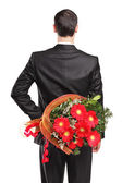 Man hiding flowers behind back — Stock Photo
