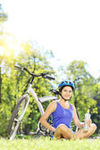 Female biker with helmet on grass — Stock Photo