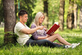 Boyfriend and girlfriend reading a book in a city park — Stockfoto