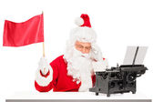 Santa Claus with typing machine waving flag — Stock Photo