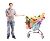Man and shopping cart with groceries — Stock Photo