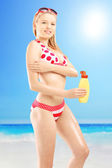 Female in bikini putting on sun cream — Stock Photo