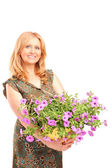 Mature female holding flowers — Stock Photo