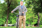 Mature man with bicycle — Stock Photo