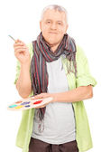 Mature artist holding a pallet and a paintbrush — Stock Photo