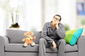 Man in pajamas thoughts on sofa — Stock Photo