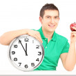 Man holding wall clock and apple — Stock Photo