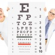 Doctor and patient standing behind eyesight test — Stock Photo #45883627