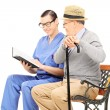 Health care professional reading to gentleman — Stock Photo #45883757
