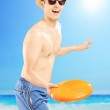 Guy in swimming shorts throwing frisbee — Stock Photo #45884185