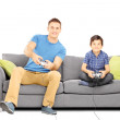 Brothers on a sofa playing video games — Stock Photo