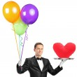 A butler holding balloons and a tray with a heart shape object — Stock Photo #45885593