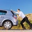 Man pushing his broken car — Stock Photo