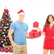 Smiling couple holding gifts — Stock Photo
