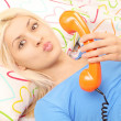 Blond woman in bed with a telephone — Stock Photo