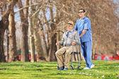 Nurse pushing senior in wheelchair — Stock Photo