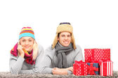 Couple on carpet near presents — Stock Photo