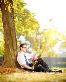 Man with flowers on grass — Stock Photo