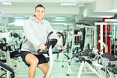 Man in a gym, exercising his legs — Stock Photo