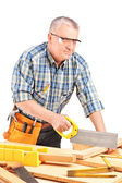 Carpenter cutting wooden batten — Stock Photo