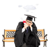 Worried student on bench holding diploma — Stock Photo