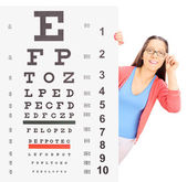 Girl with glasses behind eyesight test — Stock Photo