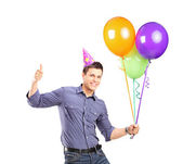 Male with party hat holding balloons — Stock Photo