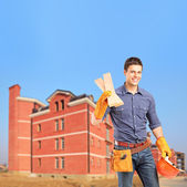 Carpenter holding sills with an apartment block — Stock Photo