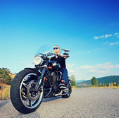 Biker riding motorcycle on road — Stock Photo
