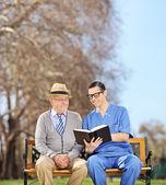 Nurse reading to pensioner in park — Stock Photo