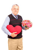 Gentleman holding heart and flowers — Stock Photo