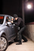 Thief with robbery mask trying to steal a car — Stock Photo