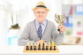 Senior chess player holding a trophy — Stock Photo