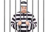 Prisoner in jail holding bars — Foto Stock