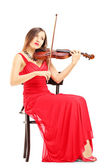 Woman in red dress playing violin — Stock Photo