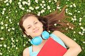 Fêmea com livro e fones de ouvido — Fotografia Stock