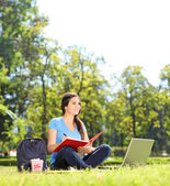 Girl sitting in park and writing — Stock Photo