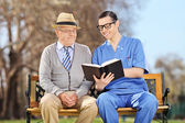 Nurse reading to pensioner in park — Stock Photo